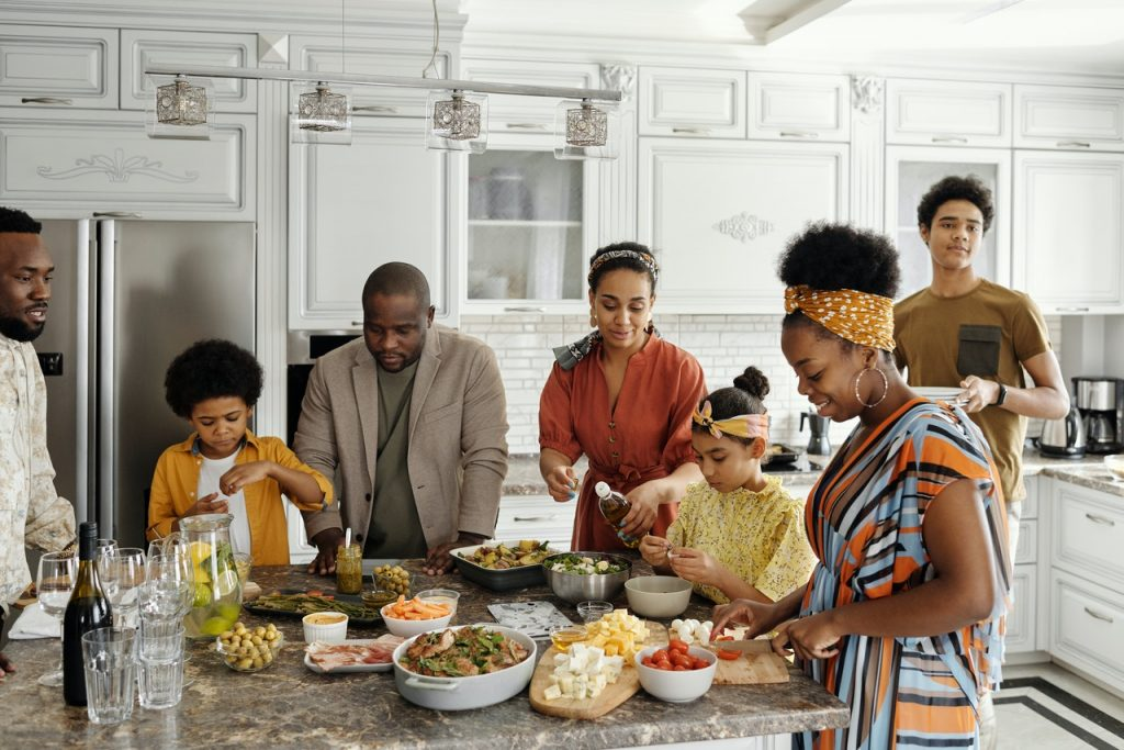 Family of all ages preparing dinner in kitchen
